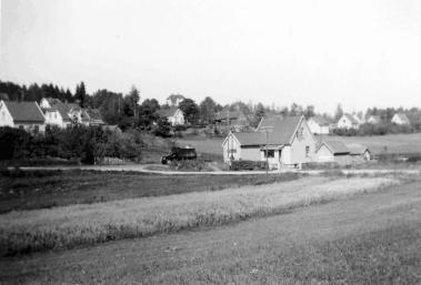 Inngangen til Holmquists butikk lå mot Kirkeveien. Huset har 1920-talls stil. Antakelig kom handelen i gang sist på 1920-tallet. Boligene til høyre i bakgrunnen (Canada) ligger til Hageveien. Det gamle huset med låve tilhørte bruket på Rønningen. Øverst i bildet skimtes boligen til lærer Reed. Den ligger fortsatt på hjørnet av Rønningveien/ Hasselveien. Bildet kan være tatt på 1950-tallet. Fotograf fra familien Holm. Eier: John Didriksen.