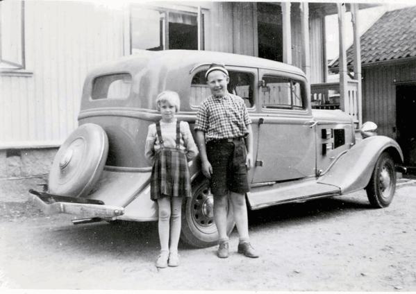Leif Olsens vare- og personbil på 1950-tallet. Her er Leifs datter Astrid og Ruths sønn Steinar Johansen foran bilen. Bilen ble brukt både til transport og fornøyelseskjøring.