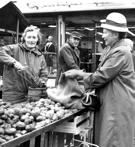 """Else Pettersen (1928) fra Bjørgestad ( gnr.702, bnr. 2) var en av Arthurs mange medhjelpere på gården. Her selger hun poteter i Fredrikstad omkring 1970. Else var ikke ukjent med gårdsdrift og potetsalg. På 1920-30 tallet kjørte faren, Jens Bjørgestad (1892-1950), fast rute med hest og vogn, hver fredag i Lislebyveien. Kunder på Lahellemoen fikk levert poteter ved døra. For datteren var turene en opplevelse. Etter endt salg fortsatte de videre mot Fredrikstad. Først var det innkjøp hos Hans Nielsen. Der handlet bøndene. Kjøpmannen kunne tilby gratis kundeparkering for hest og vogn i bakgården. Så gikk turen til Matstova hvor far og datter kjøpte skårninger. Hvetekake ble delt horisontalt i to og skåret videre i store biter. Med smør og pålegg på toppen ble dette en skikkelig """"løns"""". Søstrene Monsens kafé tilbød også skårninger. Fotograf ukjent/ØFB. Eier: Else Pettersen."""