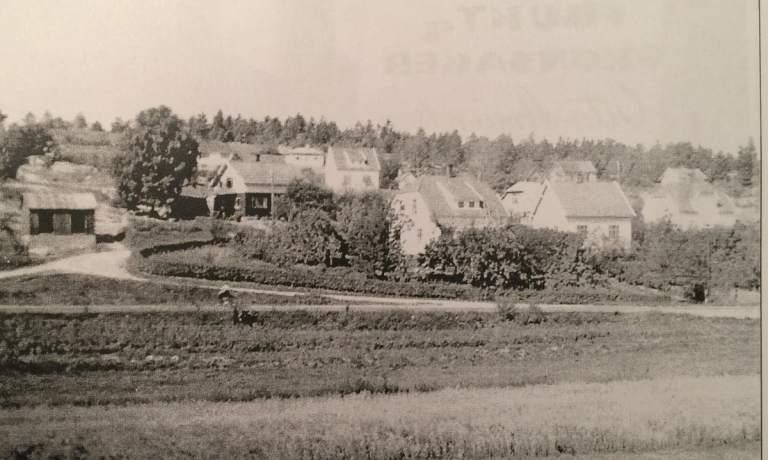 Amundsens forretningsbyggg ligger i Rønningveien, til venstre i bildet. Midt på 1950-tallet var det direkte adkomst fra og til Rønningveien fra Rolvsøyveien (Fv109). Hovedveien ligger fredfull i forkant av bebyggelsen. Foto: Familien Holm/Didriksen. Eier: John Didriksen.