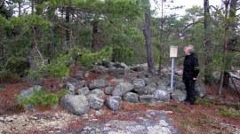 Bronsealdergrav med skilt og person. Her er gravhaugen utstyrt med skilt fra Fylkeskonservatoren. Foto: Lars Willy Corneliussen.