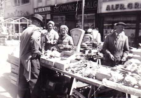 Ekteparet Molvig betjener en mannlig kunde bak et rikholdig grønnsaksbord. Forretningene i bakgrunnen er fra venstre: Lund & Tallaksen, As TEXTIL, SALOMONS UTSALG og ALFR. GRØNNEBERG. Fotograf ukjent/ØFB.