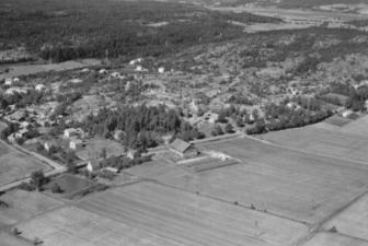 Bildet fra 1952 viser Vallefjellet og jordbruksområdene rundt gården Saxegård. Låven fra 1948 ligger midt i bildet. Det mørke feltet i venstre bildekant er restene etter den gjengrodde isdammen hvor bøndene skar is for Nøkleby meieri. Saxegård sag er lite utbygget. Den mørke stripen i høyre bildekant er Stordiket som har gitt navn til Dikeveien. Foto: Widerøe Flyveselskap/ØFB