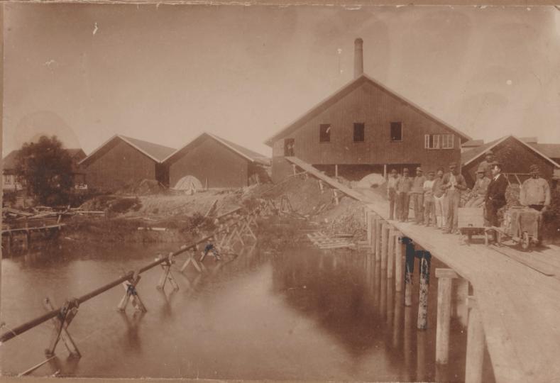 Søndre Omberg teglverk ble anlagt i 1897 av Andr. Hanestad, og ble nedlagt i 1923. Ytterst til venstre, bak trærne, skimtes formannsboligen. Grunnmuren i granitt ligger i dag nær grillplassen i gropa. Videre ser vi et tørkehus for ubrent sten, et lagerhus for brent sten, og dernest brennovnen. Tekst SGE:224.