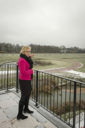 Wethouder Anja van Norel van de gemeente Zeveraar, op het balkon van een gloednieuwe VMBO-locatie, vooralsnog te midden van weilanden. Beeld Provincie Gelderland