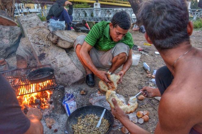Comiendo pan campesino que compraron con un revoltillo de sobras de pollo
