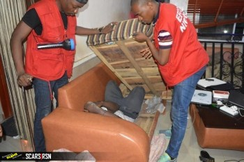 One of the suspects hiding inside a sofa