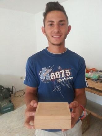 Gabi shows off the first box made in the Tigmandru Woodshop