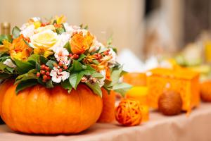 jesienna dekoracja stołu podczas przyjęcia w kolorze pomarańczowym z dyniami i kwiatami