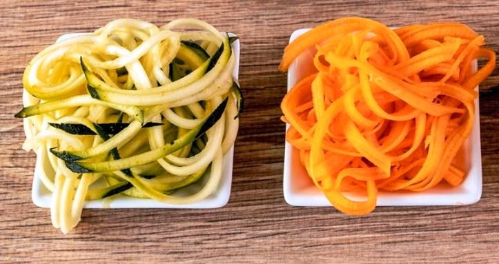 Gemüsenudeln aus Zucchini und Karotte auf weißen Tellerchen.