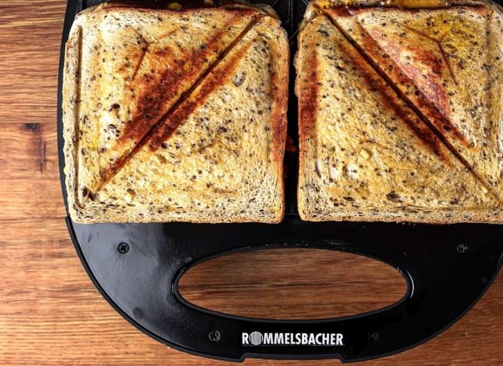 Teilansicht Sandwichmaker mit zwei knusprigen toasts befuellt.