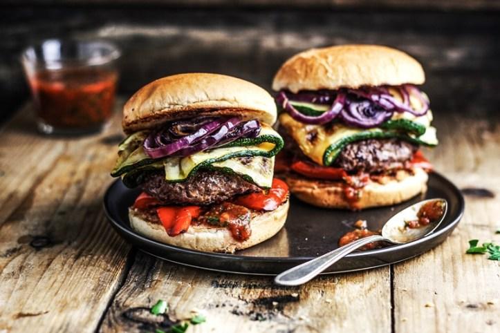 zwei Burger mit Hackpattie und Grillgemüse auf Teller und Holztisch Rommelsbacher Tischgrill