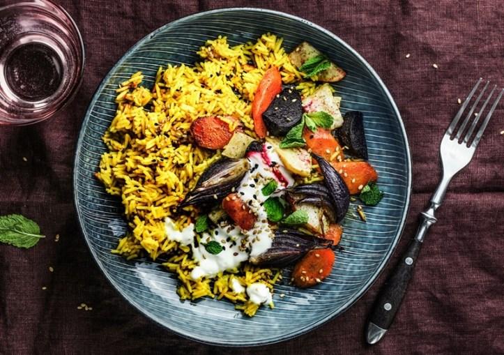 kurkuma-Reis mit Wurzelgemuese auf blauem Teller