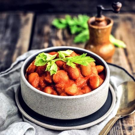 Schale mit weißen Bohnen in Tomatensauce auf Holztisch