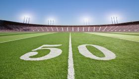 50 yard line on football field in stadium.