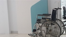 Empty Wheelchair In Corridor At Hospital