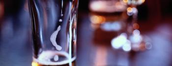 Set of car keys lying beside lager glass on bar