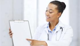 health care and medical concept - female doctor with stethoscope and blank prescription