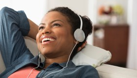 Mixed race woman listening to headphones on sofa
