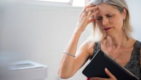 Frustrated Caucasian woman holding digital tablet suffering headache