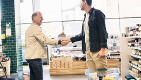 Happy men shaking hands in supermarket