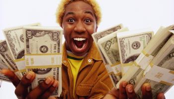 Young man holding bundles of US dollars, smiling, portrait