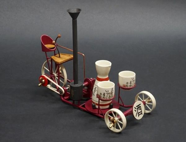 "the metal sculpture ""Seishu Cart"" a metal work art piece that doubles as a sake decanter and glass holder or bar cart"