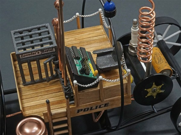 "the metalwork and wood sculpture ""Speeder's Chagrin"" a retro futuristic depiction of a police vehicle making use of a camera, spark plugs and micro controller boards in it's construction. the words POLICE and LAW ENFORCEMENT can be seen on the sides and overhang"