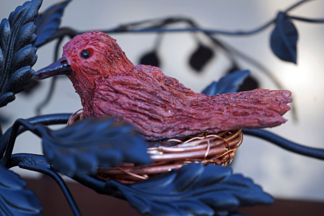 "a closeup shot of the intricate metalwork bird that sits atop the metal sculpture known as ""Mission"""