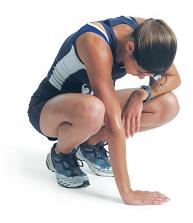 a young woman in a blue track uniform is squatting down as she leans against her knee and looks down