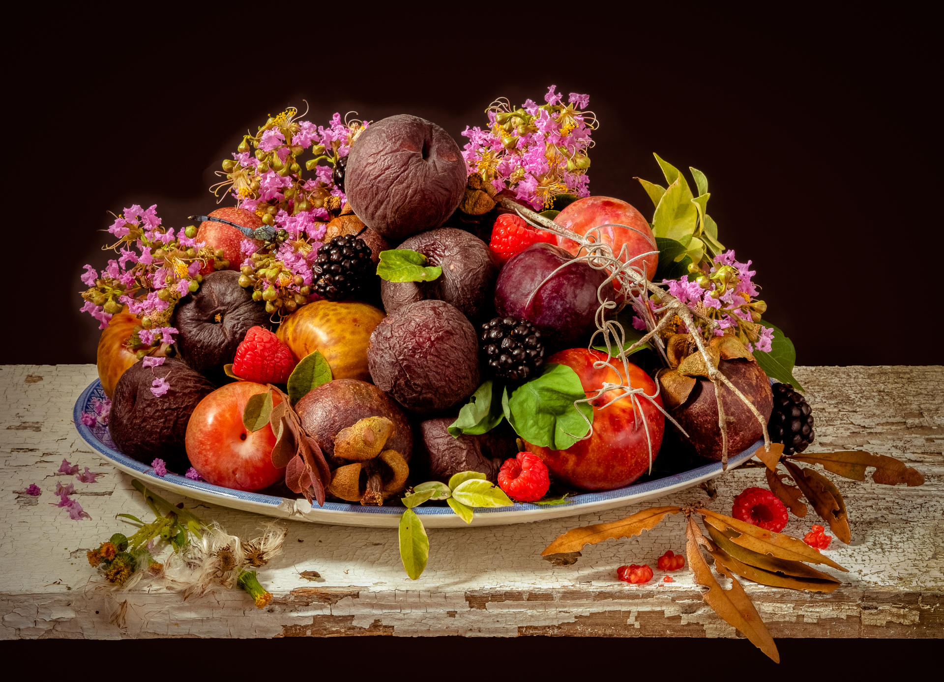 a bowl of fresh fruit with flowers - a still life photograph