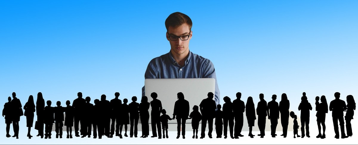 Man sitting at a computer surrounded many other people.