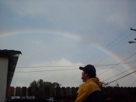 Ken in the back yard, arched by a rainbow.