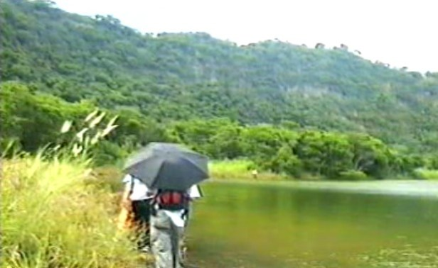 man carrying an umbrella while walking on the crater lakeshore