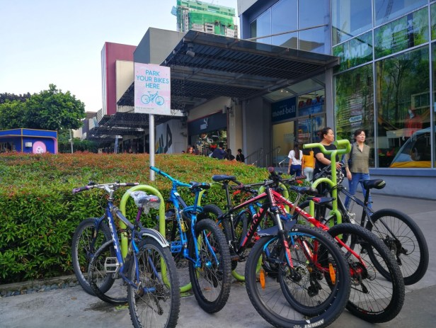 row of parked bikes in front of a mall