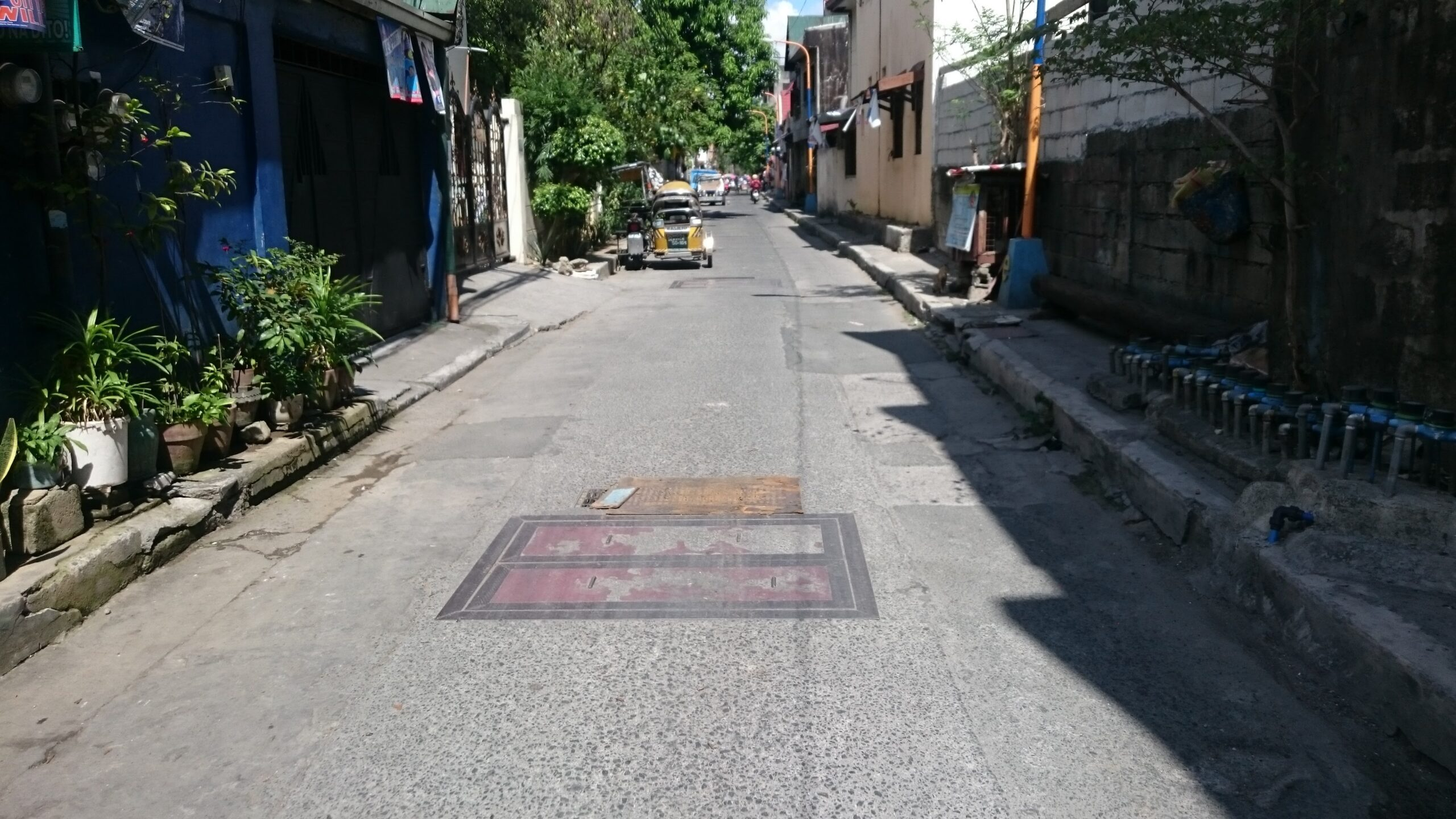 narrow road with parked tricycle and rectangular manhole covers