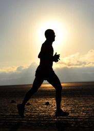 Silhouette of a runner along the beach