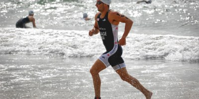 Triathlete running along beach