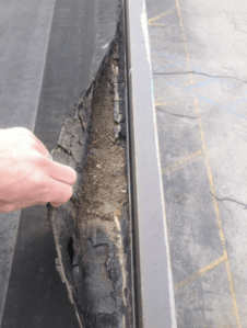 The roof edge condition on the building is coming loose. This roof is at a major risk of blowing off in high winds and has potential for major leaks.