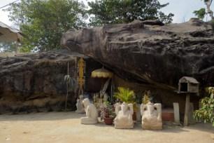 """Die Tempelanlage ist dem Hindugott Shiva geweiht, trotzdem lässt sich an vielen Stellen beobachten wie sich der Ahnen-Kult der Khmer mit den indischen Einflüssen vermischt hat. Unter diesem Gesteinsbrocken haust wahrscheinlich auch ein Geist oder Heiliger, die Statuen sind jedoch der hinduistischen Mythologie entlehnt, z.B. Ganesh, der """"Herr der Hindernisse"""" und Gott in Elefantengestalt."""