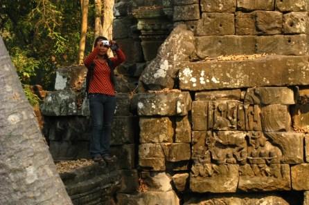 """Der Tempel stammt aus der Hochblüte von Angkor und ist eine weitere Manifestation von Jayavarman VII., dem Erbauer des Bayon-Tempels, weltbekannt durch die vierseitigen """"Gesichtstürme"""". Es wundert deshalb nicht, dass die hiesige Struktur und Architektur viele Parallelen aufweist.. Wegen der abgeschiedenen Lage war der Tempel in der Vergangenheit oftmals Opfer von Grabräubern, die zum Teil auch dafür verantwortlich sind, dass von dem eigentlichen Tempelanlagen nur noch Ruinen übrig sind."""