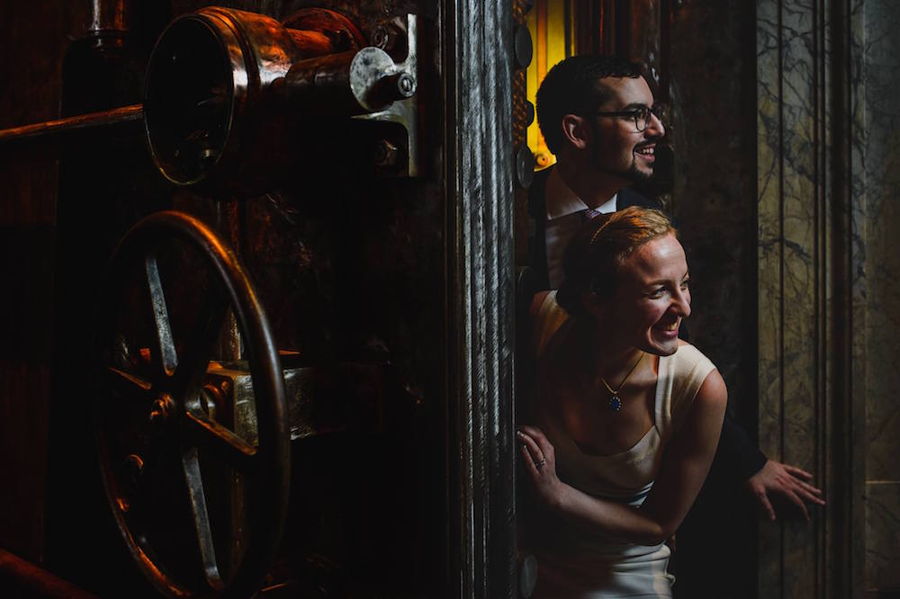 Photo of Lisa and David of Room Escape Artist in their wedding clothes dramatically escaping a bank vault.