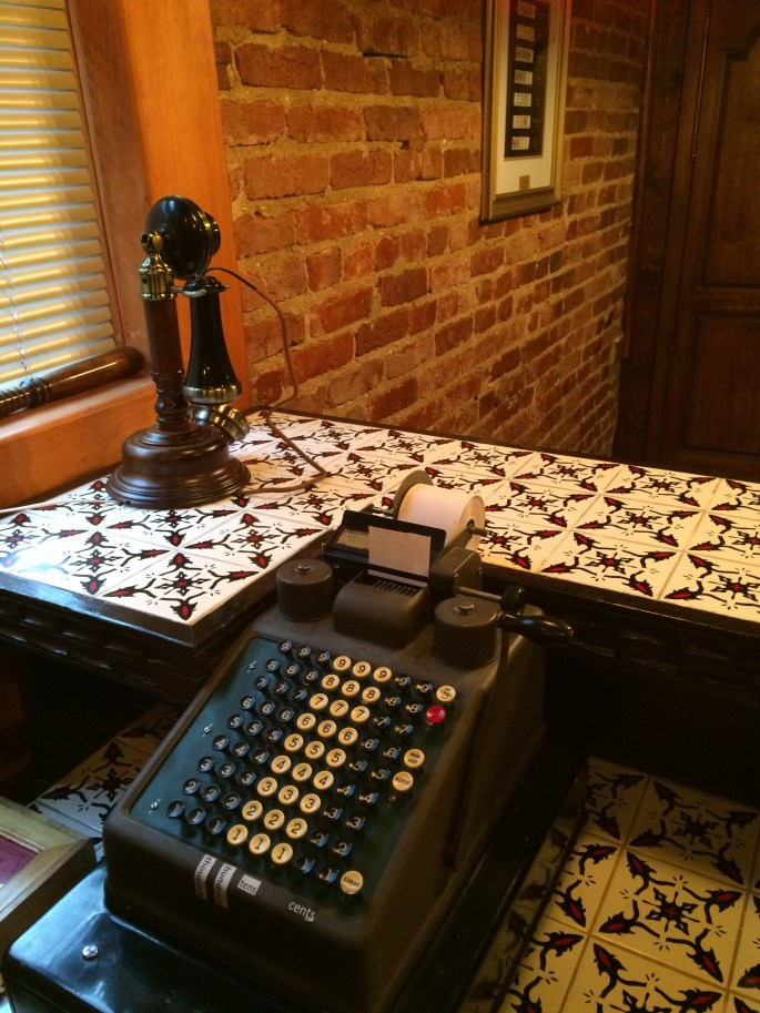 An old bar with a rotary phone, and a mechanical cash register.