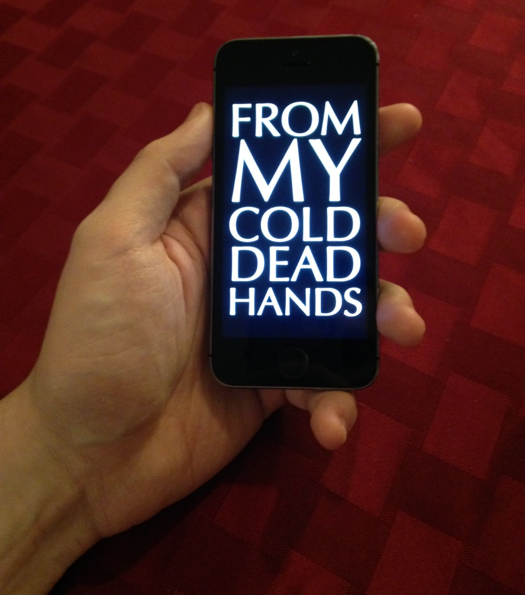 "A closeup of a hand holding an iPhone. The iPhone's screen says, ""FROM MY COLD DEAD HANDS"" in a dramatic font."