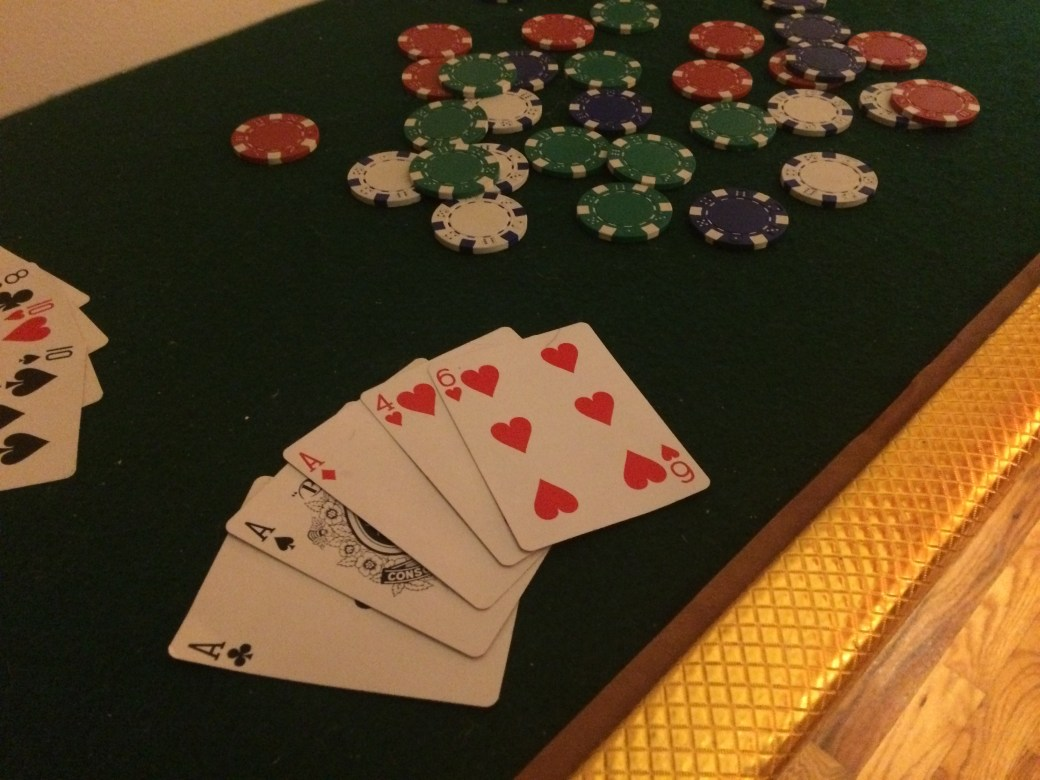 Poker table depicting a hand of cards that is a full house, and a pile of multi-colored chips.