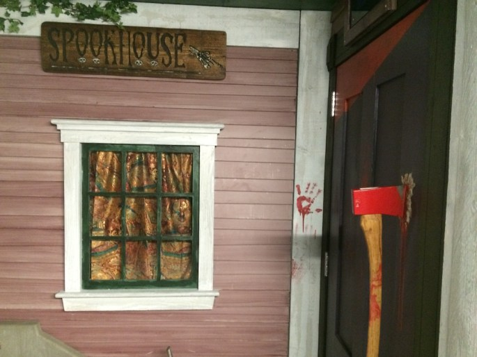 The entrance to the game Spook House. It looks like a haunted house with a bloody axe buried in the door as a handle.