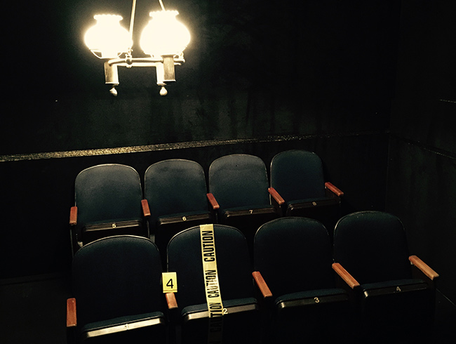 Image of 8 theater seats, one is wrapped in caution tape.