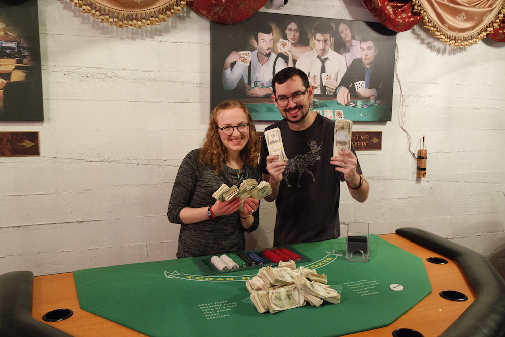 Post-game photo of Lisa and David holding stacks of money, there is a pile of cash on the blackjack table in front of them.