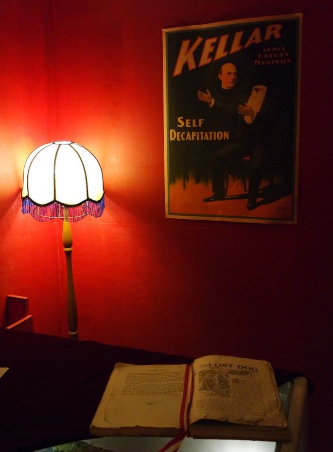 "A dimly lit room with a poster featuring the magician Keller's ""Self Decapitation."" In the foreground is an aged open book."