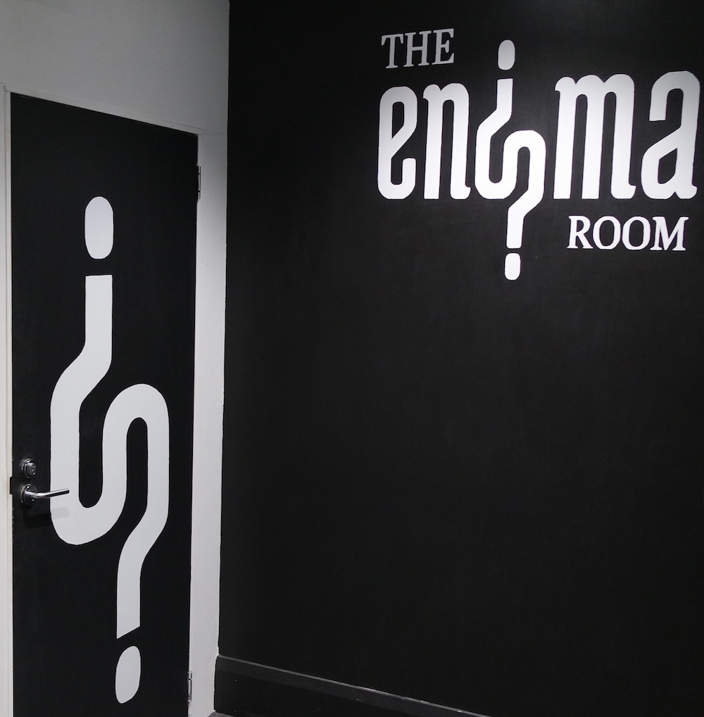 The Enigma Room's hallway. Their name is painted on the wall, their logo of intersecting questionmarks is painted on a doorway.